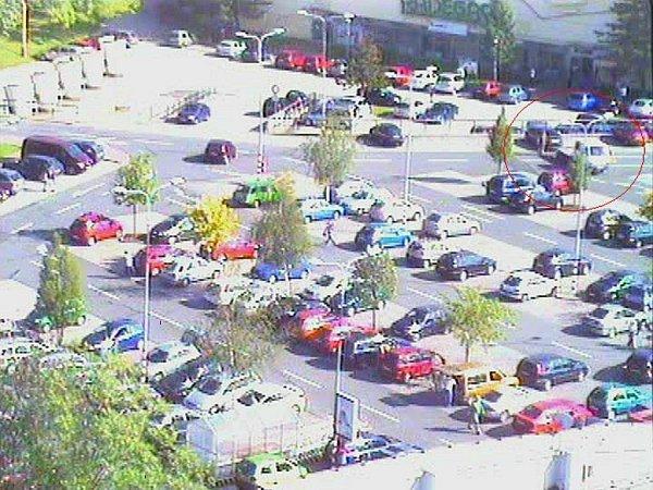 Záběr zkamery městské policie. Vpravém horním rohu je auto nakládáno na odtahové vozidlo.