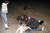 Strážníci poskytují první pomoc zraněnému muži