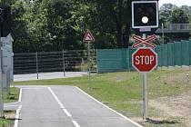Železniční přejezd se světelnou signalizací a dopravní značkou Stůj, dej přednost v jízdě.