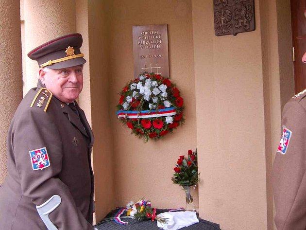 Jeden z politických vězňů položil květiny před odhalenou bronzovou pamětní deskou věnovanou obětem politické perzekuce komunistického režimu.
