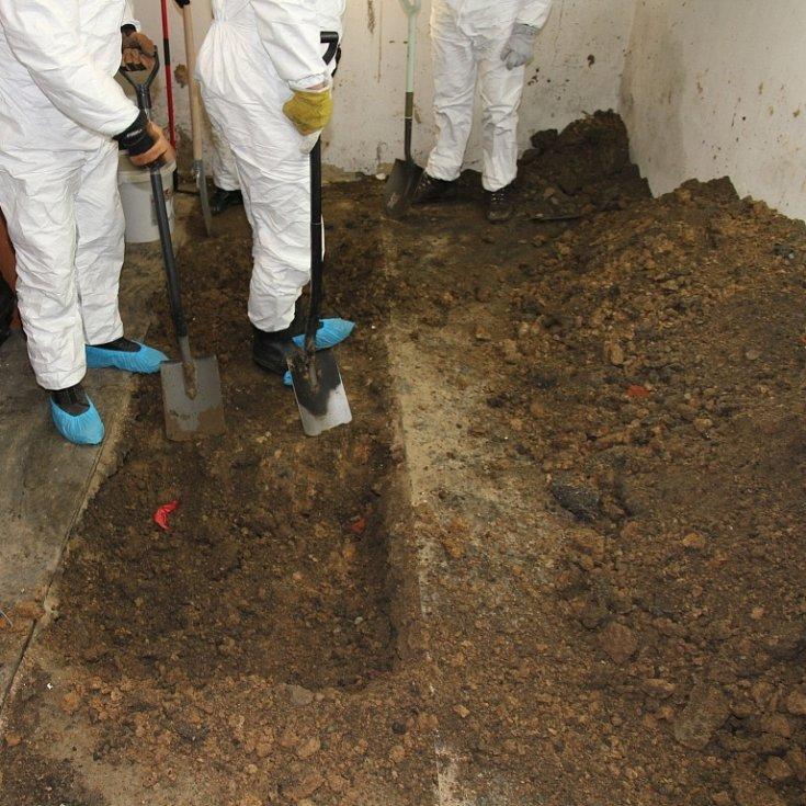 Policisté odkrývají hrob v garáži.