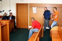 Vězeňská eskorta přivádí do jednací síně J. N., jeho komplic R. F., sedící na lavici, byl stíhán na svobodě.