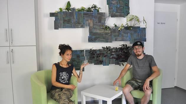 Olga Michalska a Konrád Kwieciński před zelenou stěnou v Komunitním centru Archa.