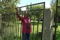 Jana Zatloukalová u plotu, který během povodní zmizel pod vodou.