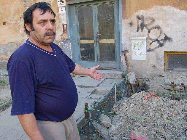 Jan Ferko ukazuje na hromadu hlíny, jež zbyla po dělnících, kteří zaváděli do domu nové rozvody elektřiny.