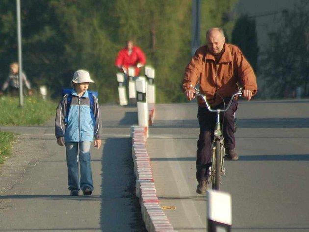 Chlapec jde po okraji silnice, kterou od provozu oddělují barevné kostky a slouží jako chodník.