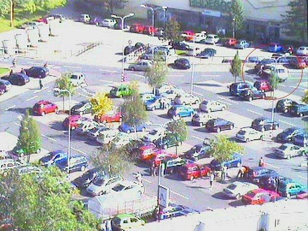 Záběr z kamery městské policie. V pravém horním rohu je auto nakládáno na odtahové vozidlo.
