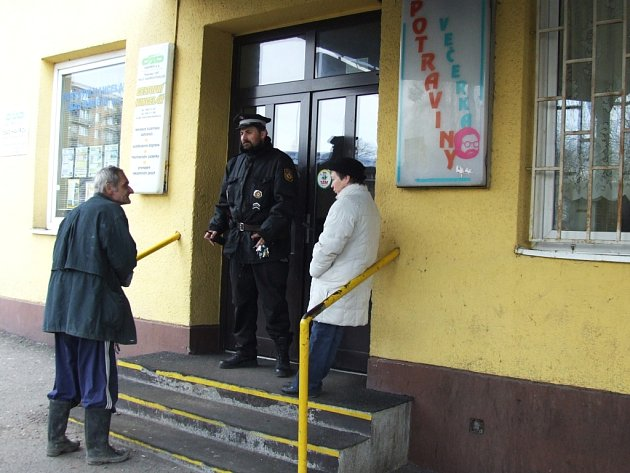 Strážník stojí před prodejnou, kterou přepadli neznámí lupiči.