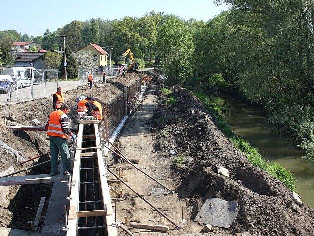 Práce na stavbě protipovodňové hráze v Petrovicích jedou na plné obrátky.