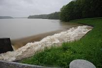 Těrlická přehrada je plná. Voda teče přes horní přeliv.
