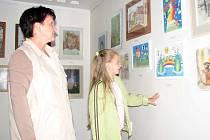 Anna Elingerová se svou vnučkou Kristinou Lavrenčíkovou prohlížejí vystavená díla žáků výtvarného kurzu.