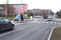 Strážník měří rychlost u přechodu pro chodce.