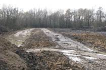 Stavba protipovodňového valu u fotbalového hřiště poblíž řeky Lučiny