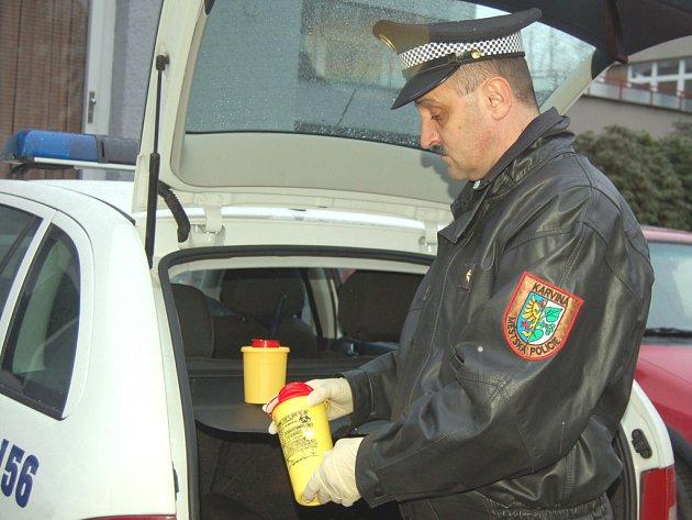 Strážník ukládá sběrné nádoby s nalezenými injekčními stříkačkami do vozu.