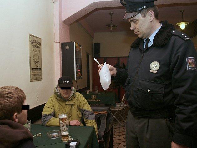 Policista kontroluje mladíky.