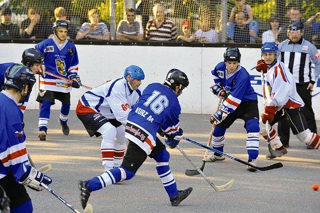 Karvinští hokejbalisté (v modrém) usilují o návrat do extraligy. Na snímku s číslem 16 Martin Kurz, vzadu vlevo přihlíží Radim Kijonka.