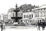 Na dobovém snímku za kašnou poblíž tramvaje je jednopatrová budova lékárny.
