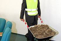 Bohumínský starosta Petr Vícha s kolečkem plným hlíny názorně předvádí rozvoz ornice. Tu město nyní lidem nabízí zdarma.