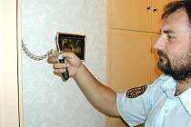 Strážník při instalaci bezpečnostního řetízku na bytové dveře.