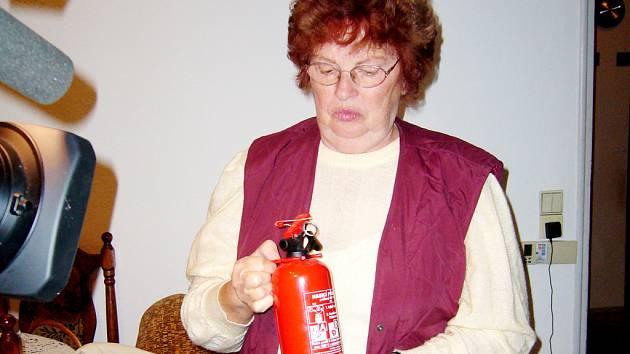 Nešťastná žena, kterou podvedli v jejím bytě v Třinci, předvádí hasicí přístroj. S protipožární dekou má za ně zaplatit třináct tisíc korun.