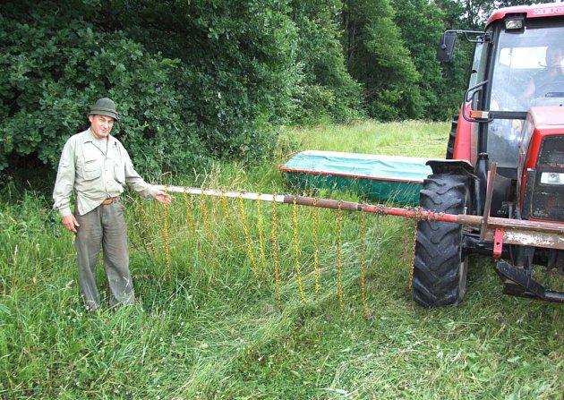 Havířovský myslivec Jan Adamek ukazuje na plašič zvěře připevněný k traktoru se sekačkou.