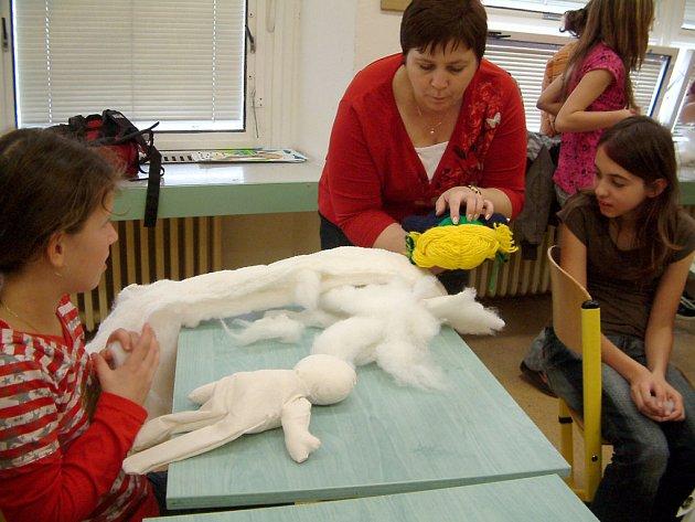 Anna Papajová ukazuje dívkám, jak si správně  počínat při výrobě panenky.