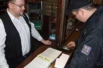 Kontrola dokladů ubytovaných hostů v ubytovně. Policista si prohlíží knihu hostů