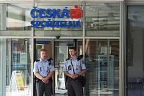Policisté hlídkují před vyloupenou pobočkou České spořitelny