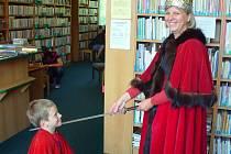 Malého Matěje Sudka pasuje na rytíře knihy jedna z knihovnic v kostýmu královny.