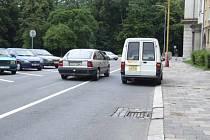 Řidiči projíždějící ulicí Na Nábřeží musejí počítat s parkujícími vozidly, s prohlubněmi u kanálů a občas také s bezohlednými pošťáky.