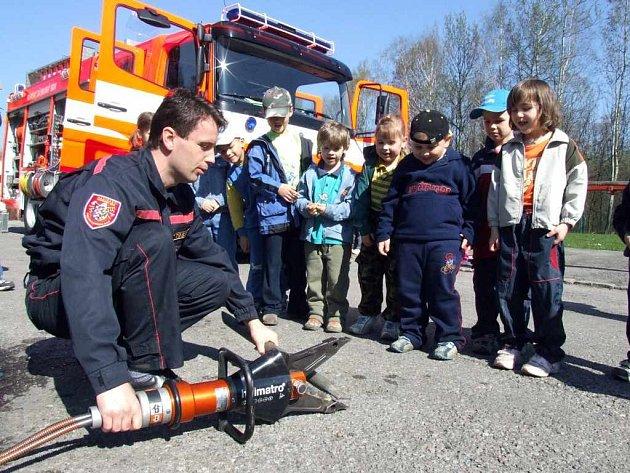 Havířovský hasič ukazuje dětem vyprošťovací zařízení.