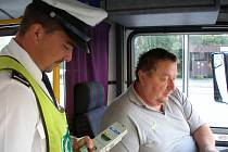 Dopravní policista kontroluje jednoho z autobusáků.