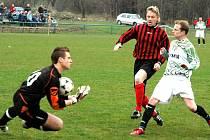 Brankář Glogár zachraňuje situaci před dotírajícím Němcem ze Starého Města (červenočerný dres).