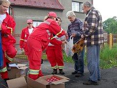 Členové Červeného kříže rozdávají lidem ze zaplavených oblastí úklidové prostředky