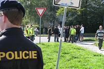 Policista dohlíží na skupinku radikálů u sociální ubytovny Merkur