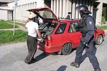 Vjezd k sociální ubytovně Merkur museli hlídat policejní těžkooděnci. Na snímku kontroluje, zda v autě nejsou kradené věci.