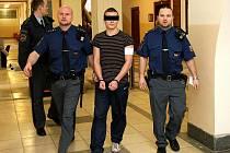 Vězeňská eskorta přivádí jednoho z obžalovaných, který v době činu ještě neměl osmnáct let.