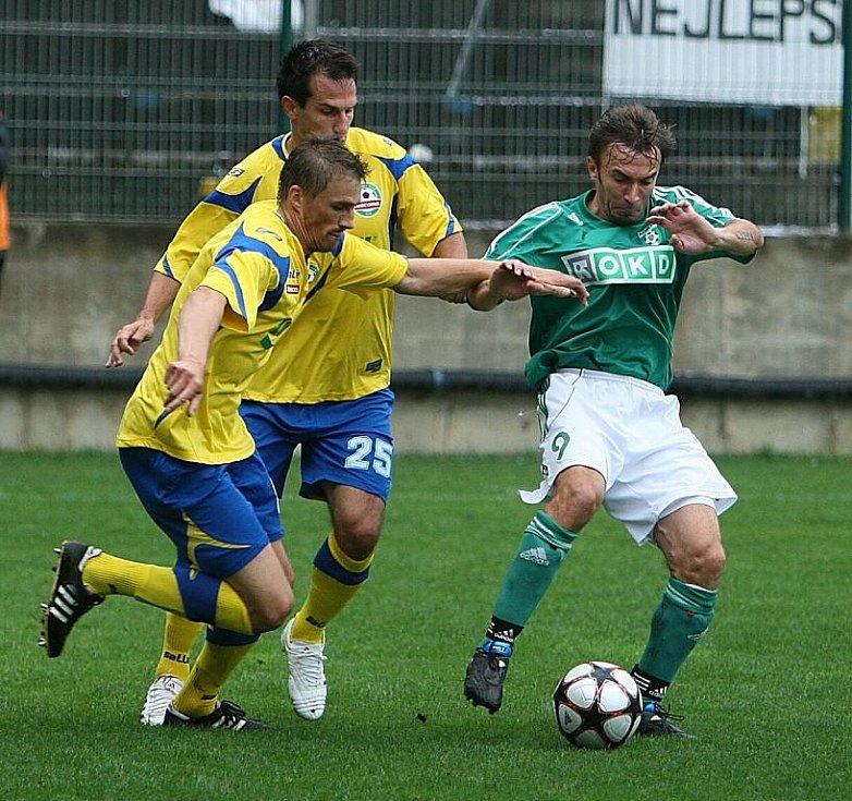 Karvinský záložník Marcel Pavlík (v zeleném) bojuje proti zlínské přesile v podání Josefa Lukaštíka a Martina Vozábala (25).