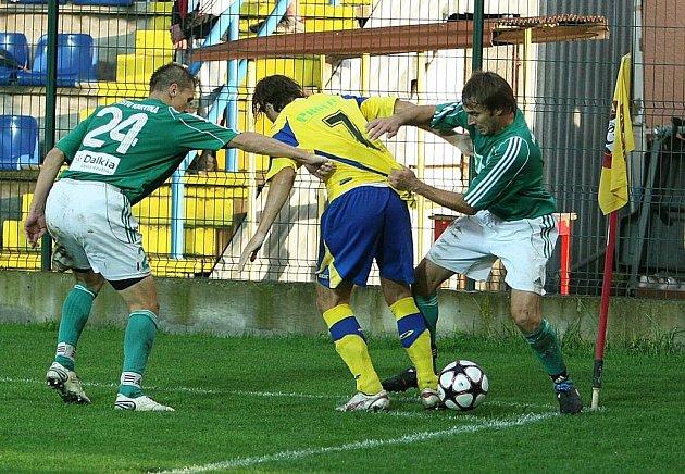 Karvinský Vladimír Staš (vlevo) a Marcel Pavlík se přetahují o dres Libora Žůrka.