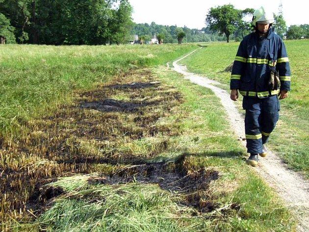 Hasič prochází kolem místa, kde starší muž úmyslně zapálil trávu.