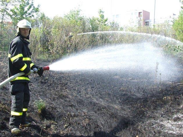 Hasič při hašení požáru suchého porostu