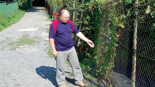 Jiří Gavenda ukazuje plot, který prý ničí fotbalisté, když se do zahrady dostávají pro míče.