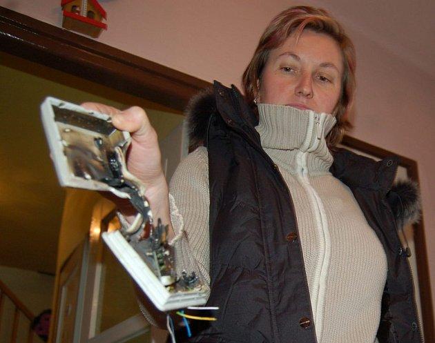 Obyvatelka Sovinecké ulice v Karviné Petra Čidalíková ukazuje vyhořelou telefonní zásuvku, do které se dostal proud.