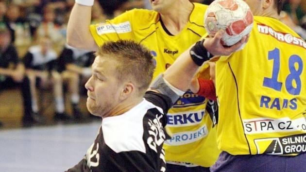 Roman Požárek (v černém) se prosazuje přes dvojblok hráčů Dukly Praha.