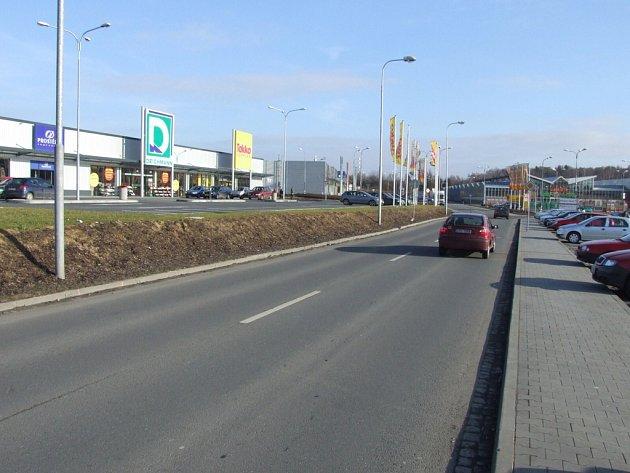Z parkoviště k obchodům nevede chodník.
