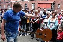 Dražitel předvádí kytaru, která se v Bohumíně nabízela k prodeji.