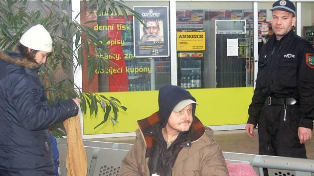 Bezdomovci se hřejí na nádraží