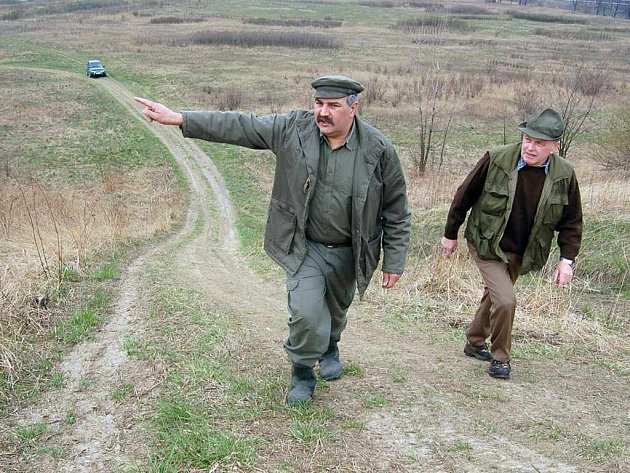 Člen místopřísežné stráže z Petřvaldu Július Štiplák (vlevo) ukazuje směrem do místi, kde vandalové na motorkách vyjíždějí v lesích nové cesty.