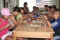 Děti ve vestibulu knihovny vyrábějí korálky.