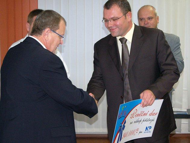 Primátor Tomáš Hanzel (vpravo) předává řediteli rájecké nemocnice Miroslavu Janečkovi šek na 940 tisíc korun.